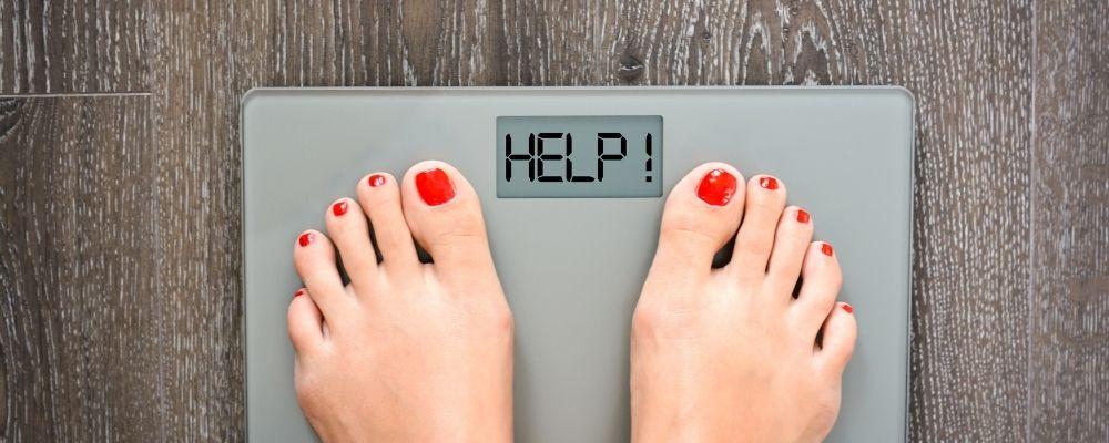 Weegschaal waar help op staat door gewichtsverlies
