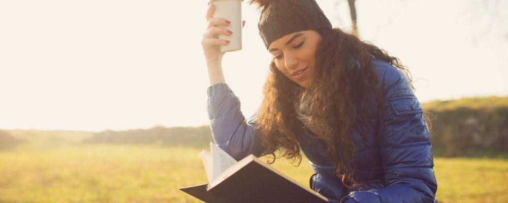 Vrouw zit buiten en leest een boek