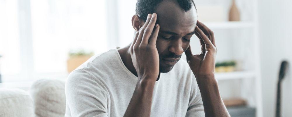Man met handen tegen zijn hoofd en hoofdpijn door overwerkt zijn