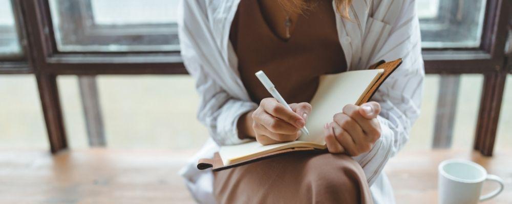 Vrouw schrijft in haar dagboek waar ze alles bijhoudt
