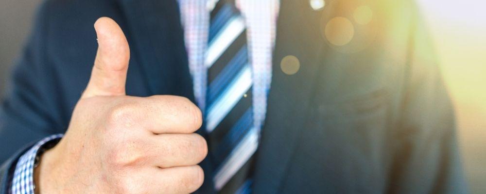 Man in pak die zijn duim omhoog steekt als goedkeuring