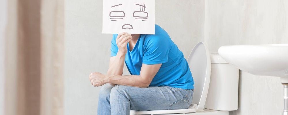Man die last heeft van constipatie met een bord voor zijn gezicht