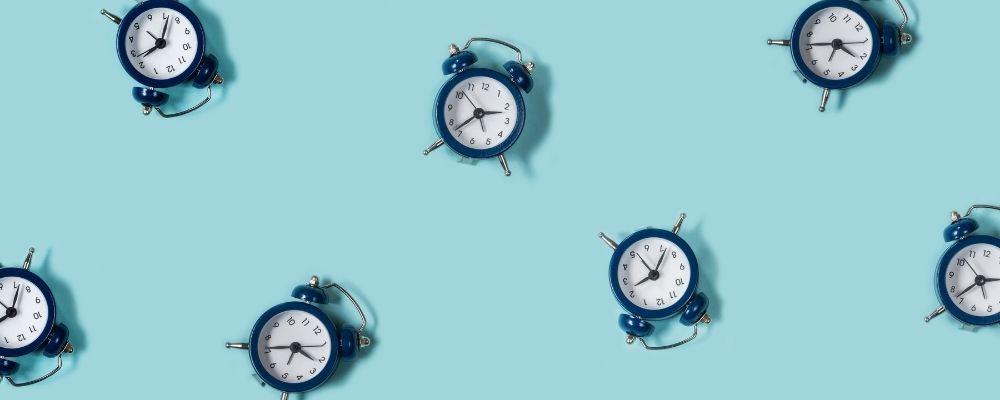 Verschillende wekkers op een blauwe achtergrond
