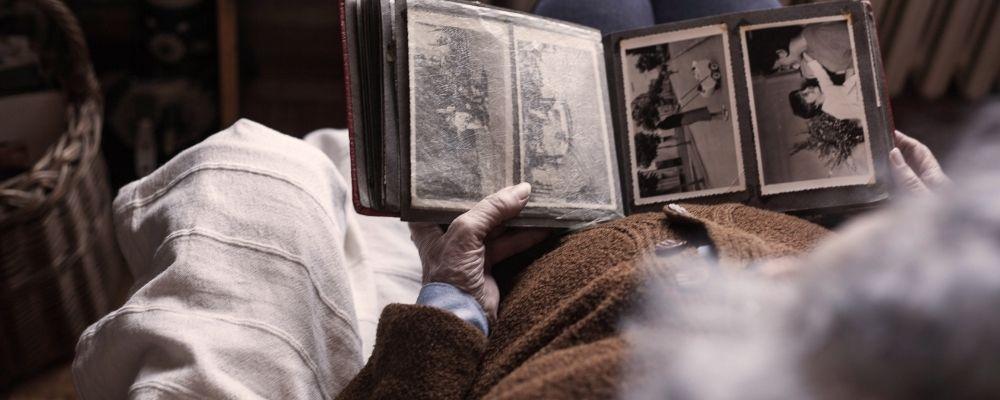 Oude vrouw kijkt naar nostalgische foto's