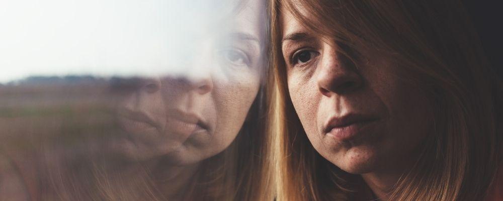 Vrouw leunt tegen een raam en voelt zich schuldig omdat ze overwerkt is
