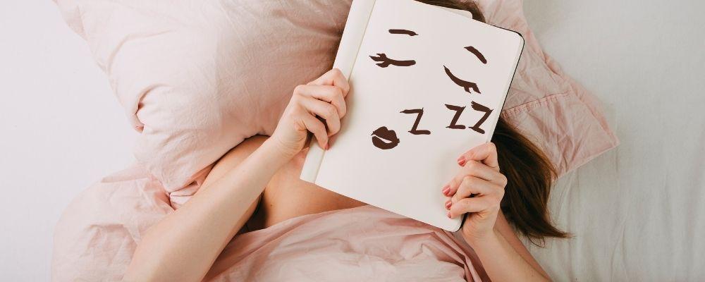 Vrouw ligt in bed met een bordje met een slapend gezicht erop voor haar gezicht