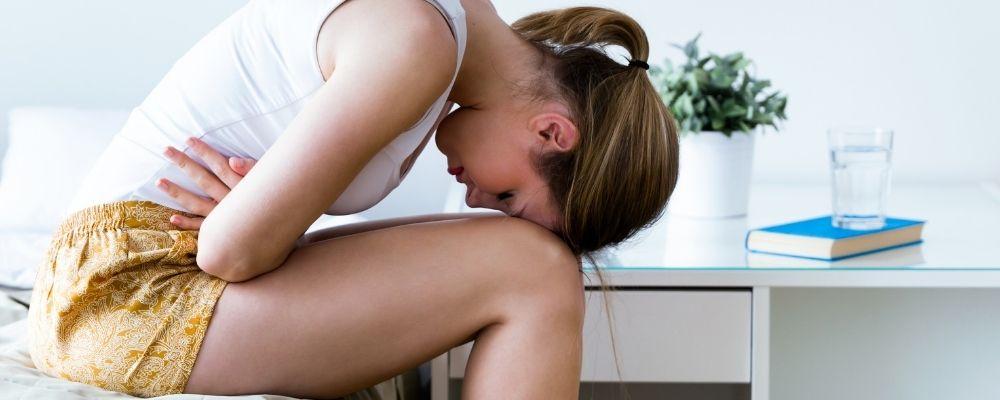 Overwerkte vrouw heeft handen op haar maag en buigt voorover