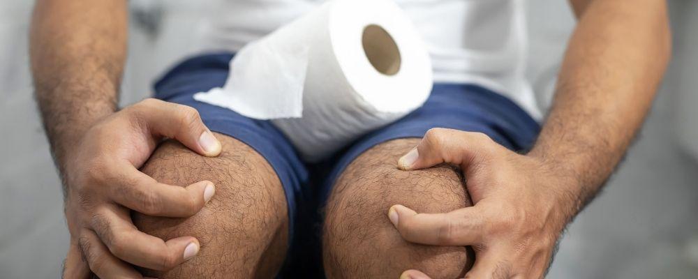 Man met buikpijn en constipatie op de wc